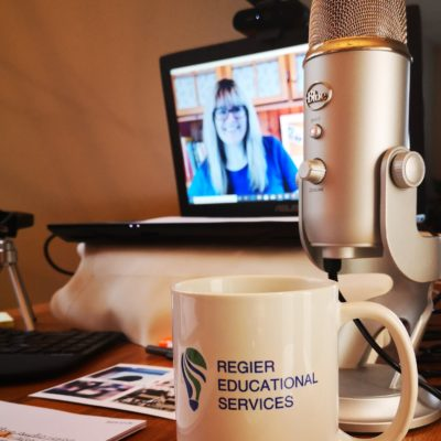 patricia shown on computer screen, showing her desk, mic, mug and set up for an online workshop