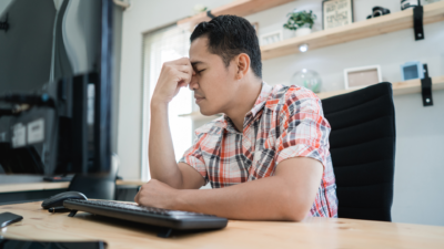 man disappointed when looking at computer screen