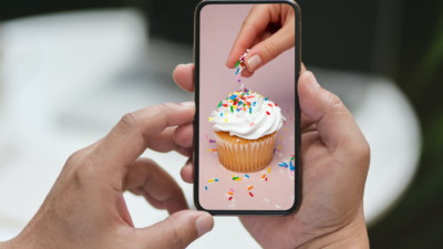 person sprinkling a cupcake, person watching it on their phone.